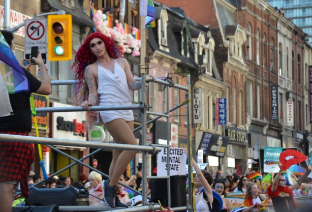 a person in a long red wig and a short white dress is posing for a male photographer on a float in the pride parade, people walking behind the float