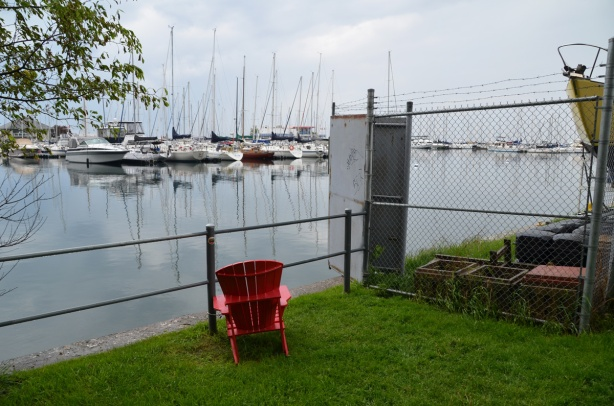 a lone red Muskoka chair sits on an angle in a small grassy patch between a fence and a path, looks out over a yacht club