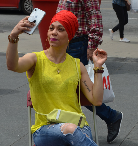 a woman in a bright yellow T-shirt, sitting on a chair, taking aselfie of her with her new red turban