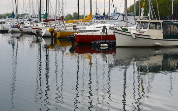 reflections of sailboats and their masts in Lake Ontario, boats are parked at a yacht club