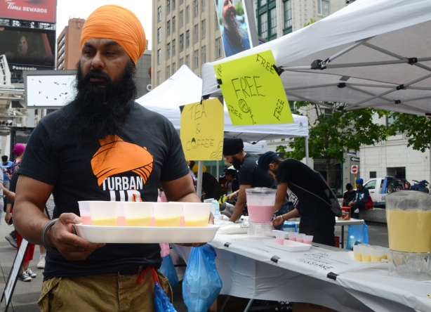 a sikh man in bears and orange turban carries a tray of cups of mango and rose milkshake