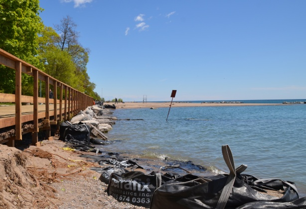 sandbags, some empty, line the shore up against rocks and a boardwalk with a railing, flooded,