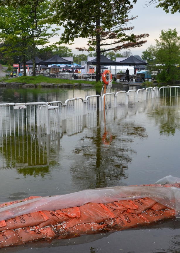 flooding at Ontario place, orange sandbags and a fence that is partially submerged in the water