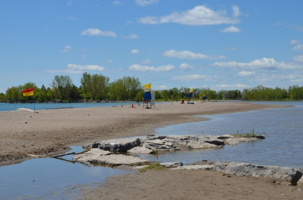 rocks and sand at Woodbine Beach, with water behind the lifeguard stations because of flooding of Lake Ontario