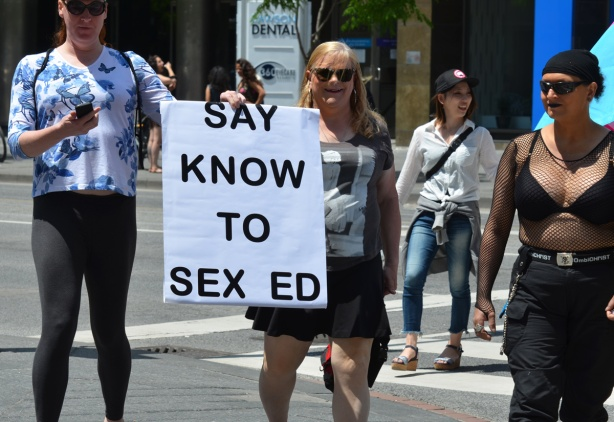 people at dyke march with large sign that says Say know to sex ed