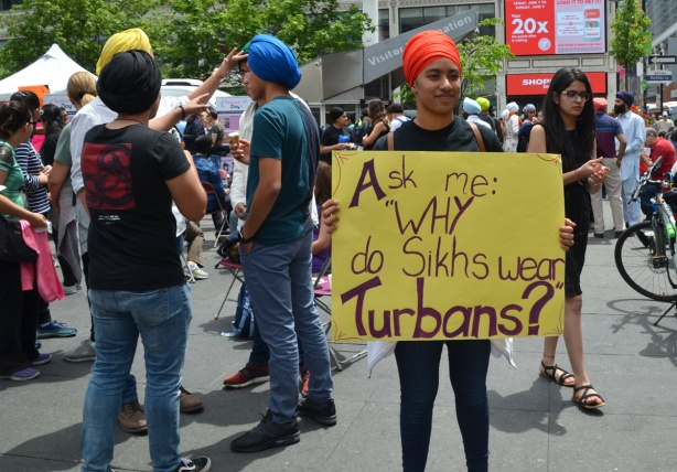 a woman holds a yellow sign that says Ask me why sikhs wear turbans