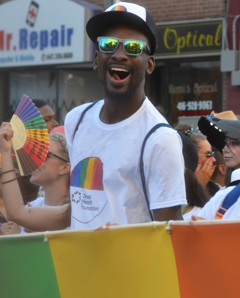 a young black man with black baseball cap and green sunglasses has a big smile as he helps carry a banner in the pride parade