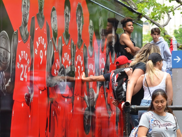 Raptors fans, parade day, leaning against the side of truck decorated with larger than life size pictures of Raptors players
