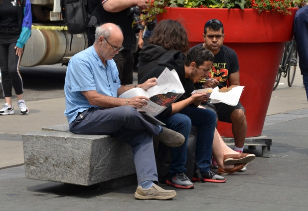 people sitting on a bench by large red flower pot in Dundas Square. Man at end, balding with grey hair, is reading a newspaper, two people are eating