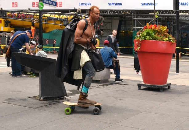 a topless man with a bag on his back skate boards at Dundas Square