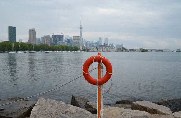 In the background is the Toronto skyline from Trillium Park, from the green trees of Coronation Park on the left and past the CN Tower and tall city center buildings, to the National Yacht Club and then Billy Bishop airport on the far left. In the foreground is an orange lifesaving ring and the rocks of the shoreline of the park