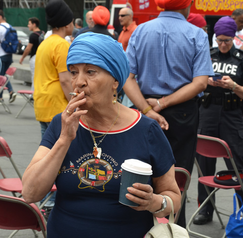 an older woman in a light blue turban smokes a cigarette