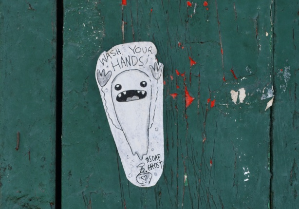 a small paste up on a green fence that is soap ghost, words say wash your hands