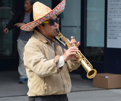 a man wearing a sombrero plays a tenor sax outside, street musician