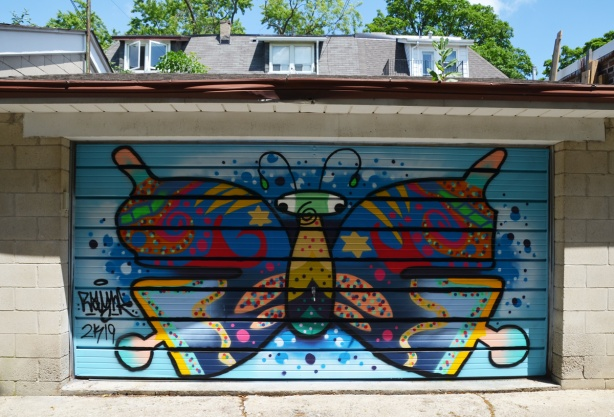 stylized butterfly with lots of colours and spots, on a garage door