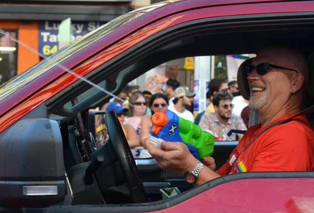 a man driving a red vehicle is spraying people out the window with a super soaker