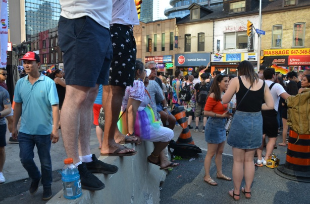 two men standing on a concrete barrier, watching parade, other people on the sidewalks