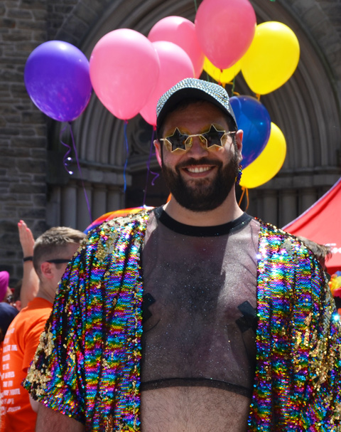 a man with bare midriff, beard, mustache, and star shaped sunglasses poses in front of a bunch of balloons