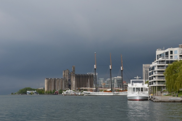 Canada Malting Company old concrete silos on Toronto Waterfront, la large boat docked near the foreground, dark skies over Lake Ontario as a storm approaches