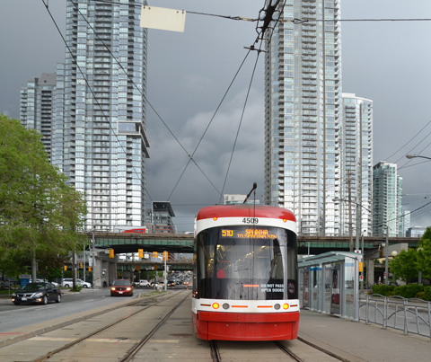 a new TTC streetcar starts to head north on Spadina, just south of the Gardiner and large condos