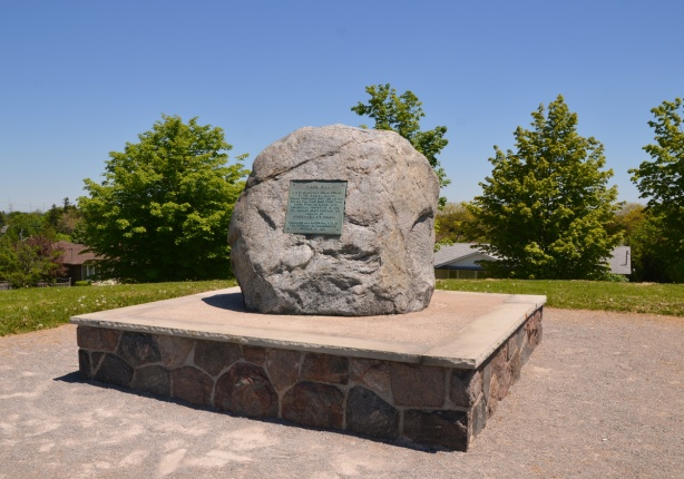 a large rock wits on a stone and concrete platform on the top of a grassy hill, Taber Hill memorial