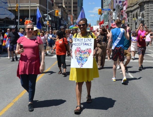 women walking in dyke march, one woman in a bright yellow dress carrying a sign that says teach love and acceptance, with a heart made of people