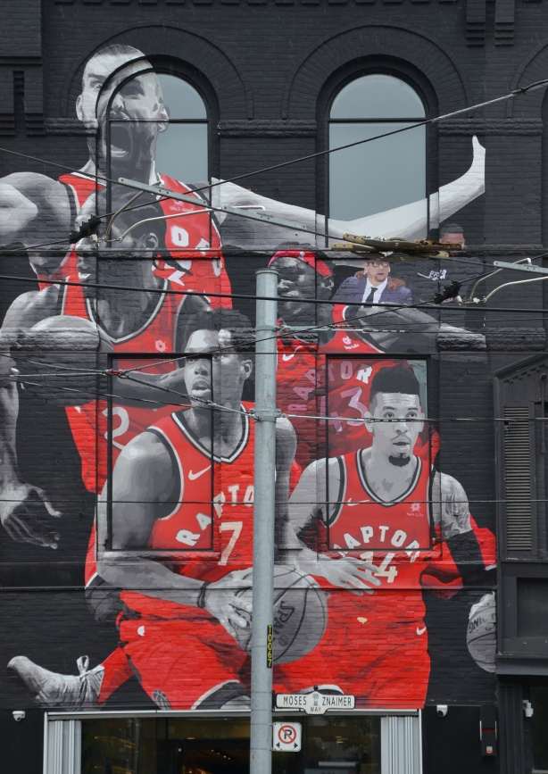 mural of the Toronto Raptors, 5 players in their red uniforms along with the coach and Drake. On a storefront on Queen Street West.