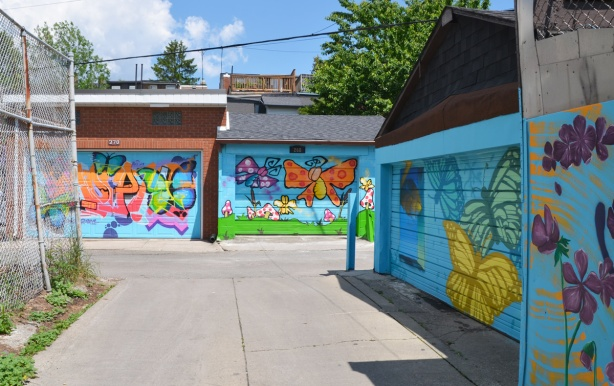 three butterfly murals on three garage doors in an alley