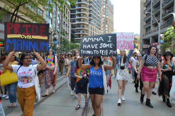 dyke march 2019, three women holding three signs while marching in parade
