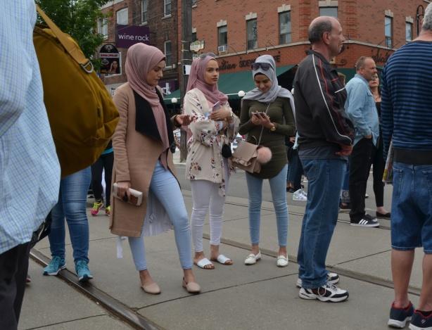 three muslim women in head scarves on the street, street festival