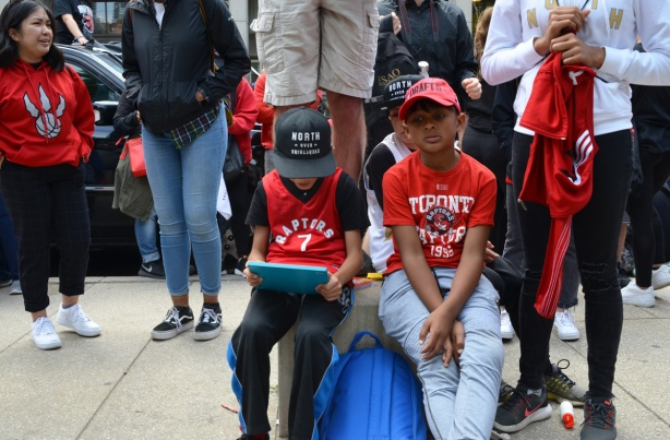 Raptors fans, parade day, three boys sitting, looking tired and bored, in Raptors T shirts and baseball hats