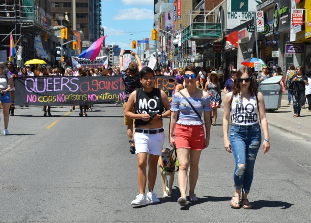 three women walking in dyke march in front of a group with a banner that says queers against borders
