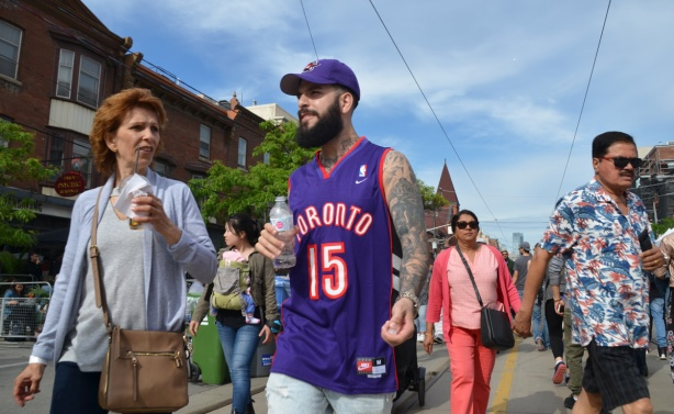 people walking down the street towards the camera, a man in a purple Raptors shirt with marching baseball cap, a woman in a light blue blouse with a drink in her hand, a woman in a pink pant suit