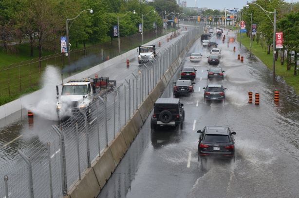traffic on Lakeshore Blvd plows through the water and creates great splashes of water, road is partially flooded
