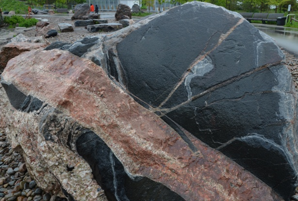large chunk of granite in a park, black patches with streaks of pink and grey