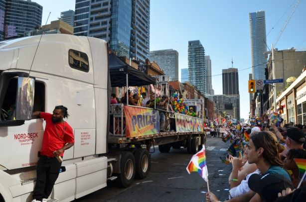 a man in a red shirt stands by the drivers door of a white truck as it pulls a float in the pride parade, going down Yonge street with many people on the sidewalk watching