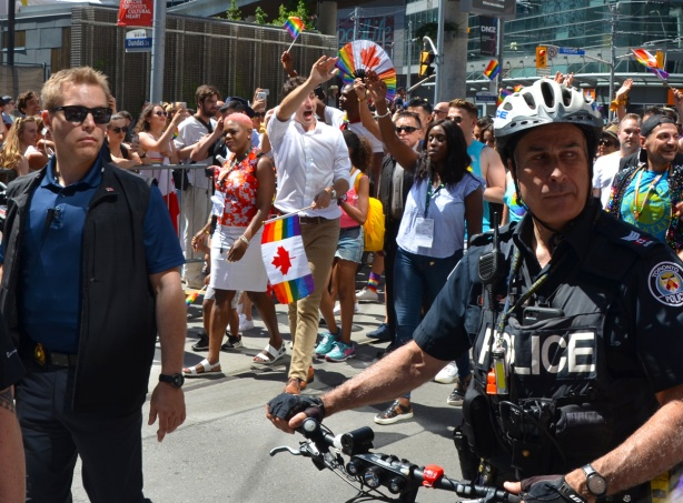 Prime Minister Justin Trudeau walks in the pride parade in Toronto with other people, waving to the crowds, police men and security detail also in the picture