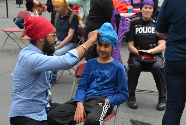 At Turbanup event at Yonge Dundas Square, a man in beard and red turban wraps the head of young person in a blue turban, in the chair behind is a female police officer having her head wrapped in a purple turban