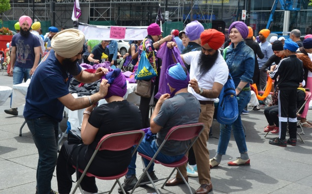 At Turbanup event at Yonge Dundas Square, people having turbans tied on their heads with purple fabric