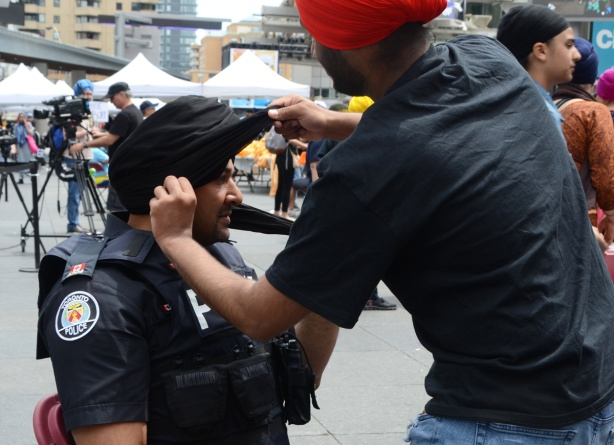 a policeman getting a black turban at Turbanup event at Yonge Dundas Square,