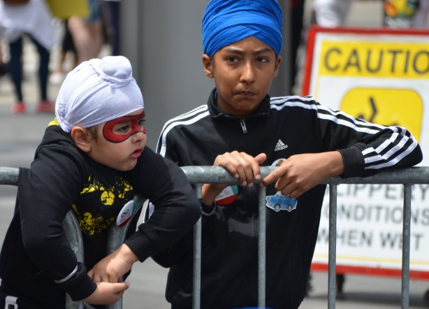 two young boys in turbans, one in blue and the other in white. The younger boy, in white, has a red mask face painted around his eyes