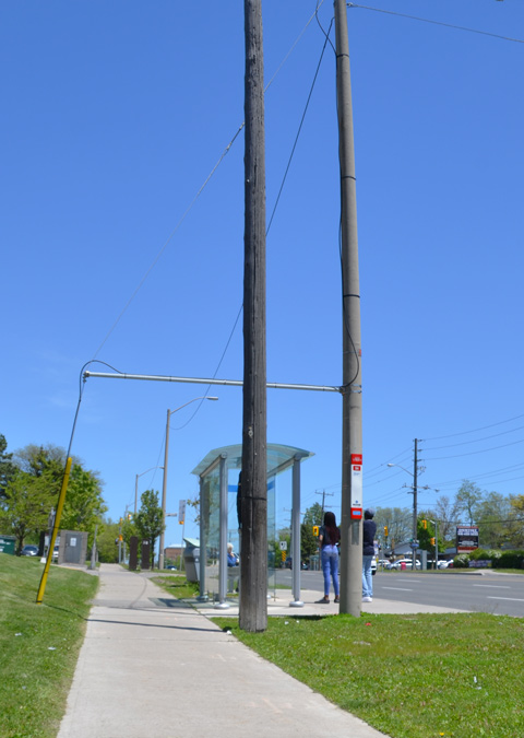 two large utility poles side by side beside a sidewalk and a bus shelter. Two people waiting for a bus