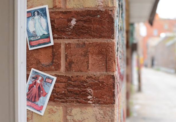 two cars stuck into the crack formed between a door and a wall, two witch cards,