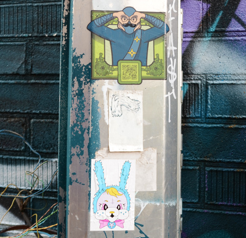 three stickers and paste ups on a metal post, urban ninja warrior on the top, with a black mustache, and a pink and blue bunny face on the bottom