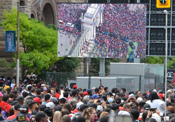 a large video screen shows progress of a parade, crowds watching it