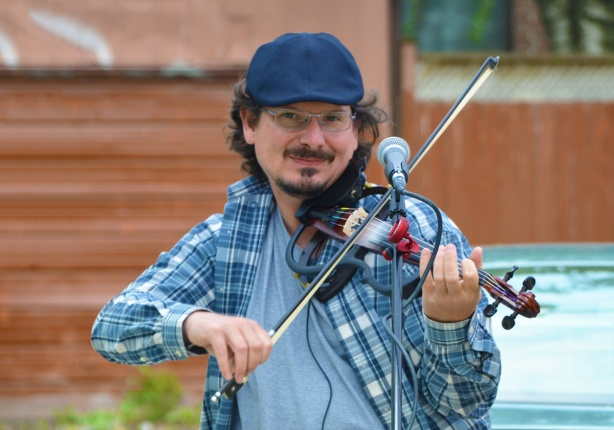 a man playing a fiddle, smiling, wearing a blue cap and a blue plaid shirt