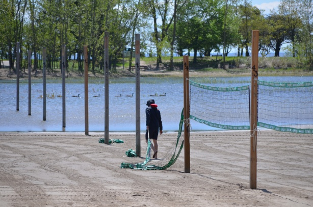 a man is putting up volleyball nets on the poles that aren't in the water at a flooded Woodbine Beach