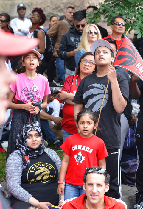 Raptors fans, parade day, sitting on street and sidewalk, watching a video screen showing the parade as it makes its way towards Nathan Philips Square