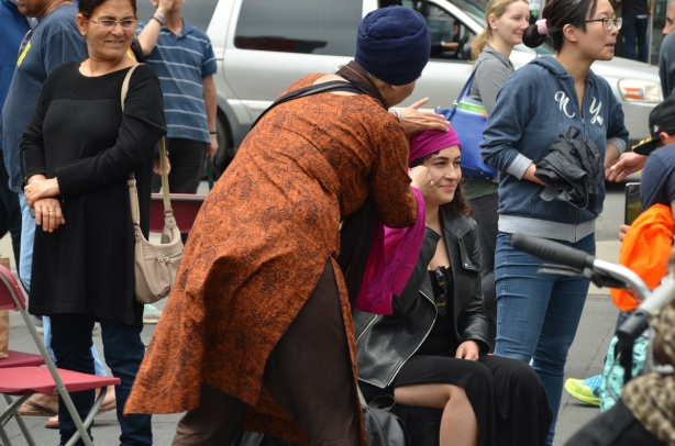 a woman watches another woman getting a turban
