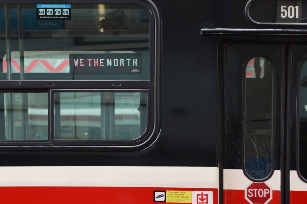 in the window of a TTC streeecar is a we the north sign